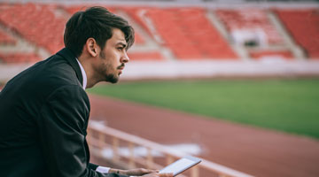 Young professional man sitting in stadium viewing statistics on tablet