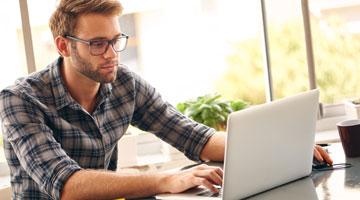 Young professional man analyzing statistics on laptop