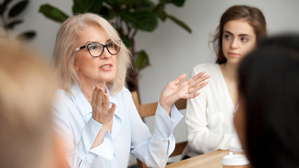 A lady with glasses speaking in a meeting.