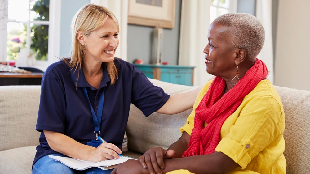 A social worker sitting on a couch while speaking to a client