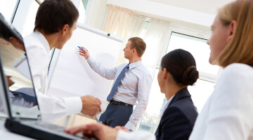 Man pointing on white board while giving a training class
