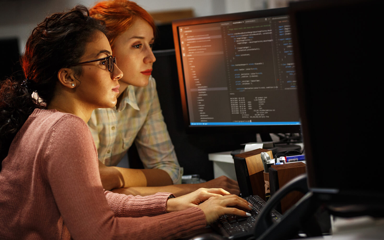Two devops personnel working on computer