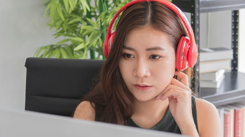 A female student studying with headphones on
