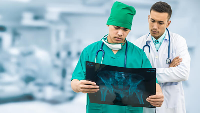 A surgeon and a doctor look at patient x-rays together.