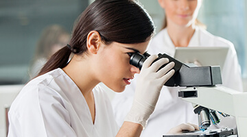 Medical technician looking through scope