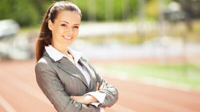 Young professional in business attire smiles in confident pose on track field.