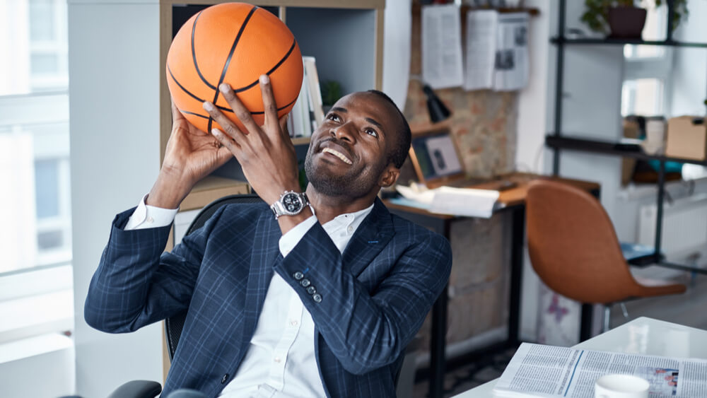 Sports manager handles basketball while sitting at his desk.