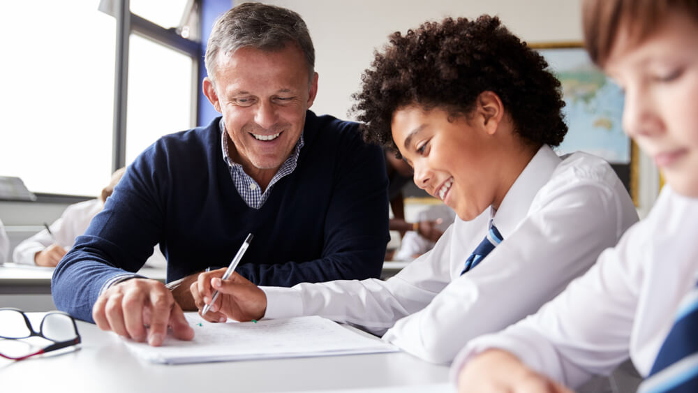 A teacher focuses on work with a student while at a desk.
