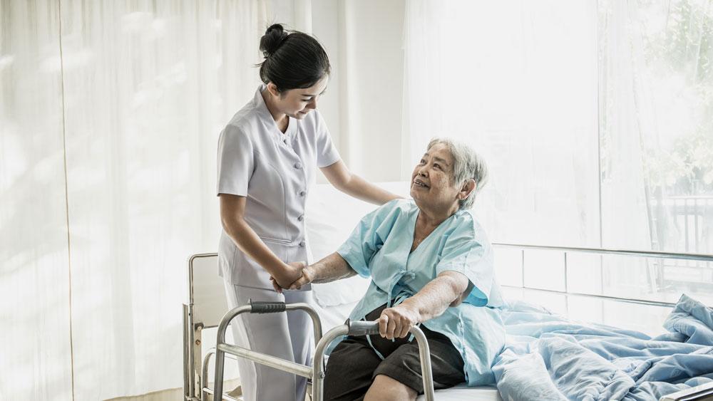 Nurse attending to elderly woman