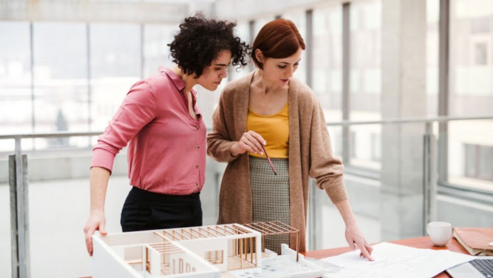 Two women in construction management stand in an office next to a model of a building on a table, discussing a blueprint.