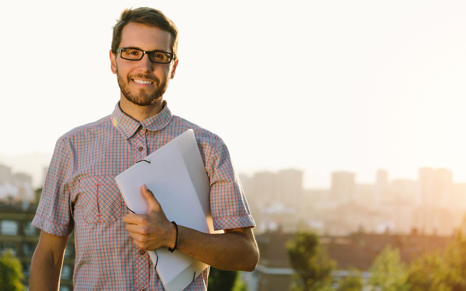 Man holding a laptop smiling