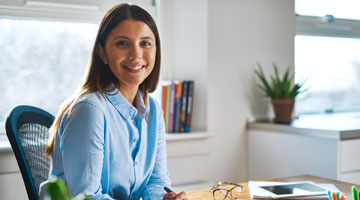 Woman sitting at her desk smiling