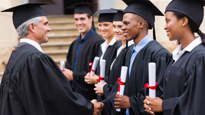 College dean awarding diplomas to graduates.