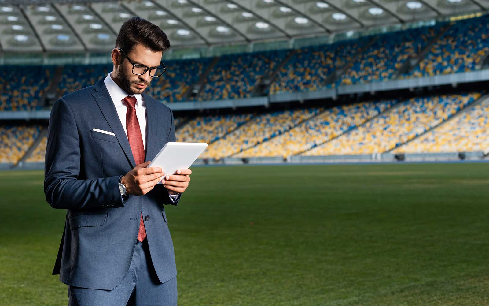 Sport administrator on the field looking at his tablet