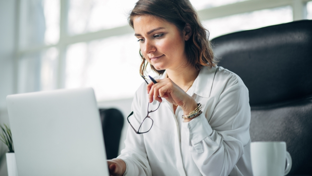 woman looking at a laptop- working on public administration