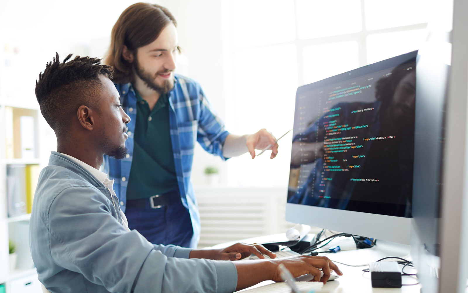 Two DevOps programmers looking at computer code