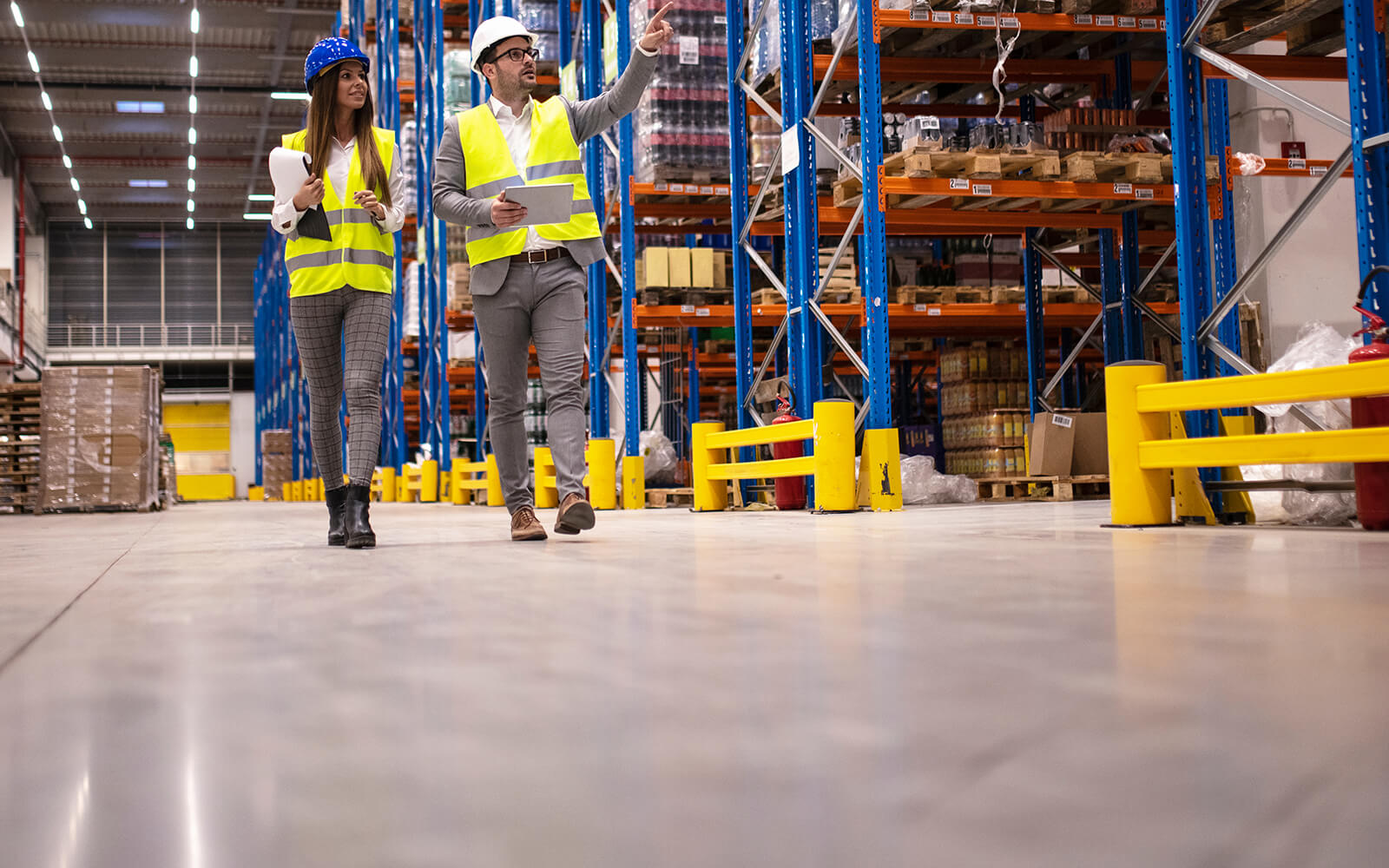 Safety manager walking with employee in warehouse