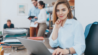 Business administration woman graduate working on laptop