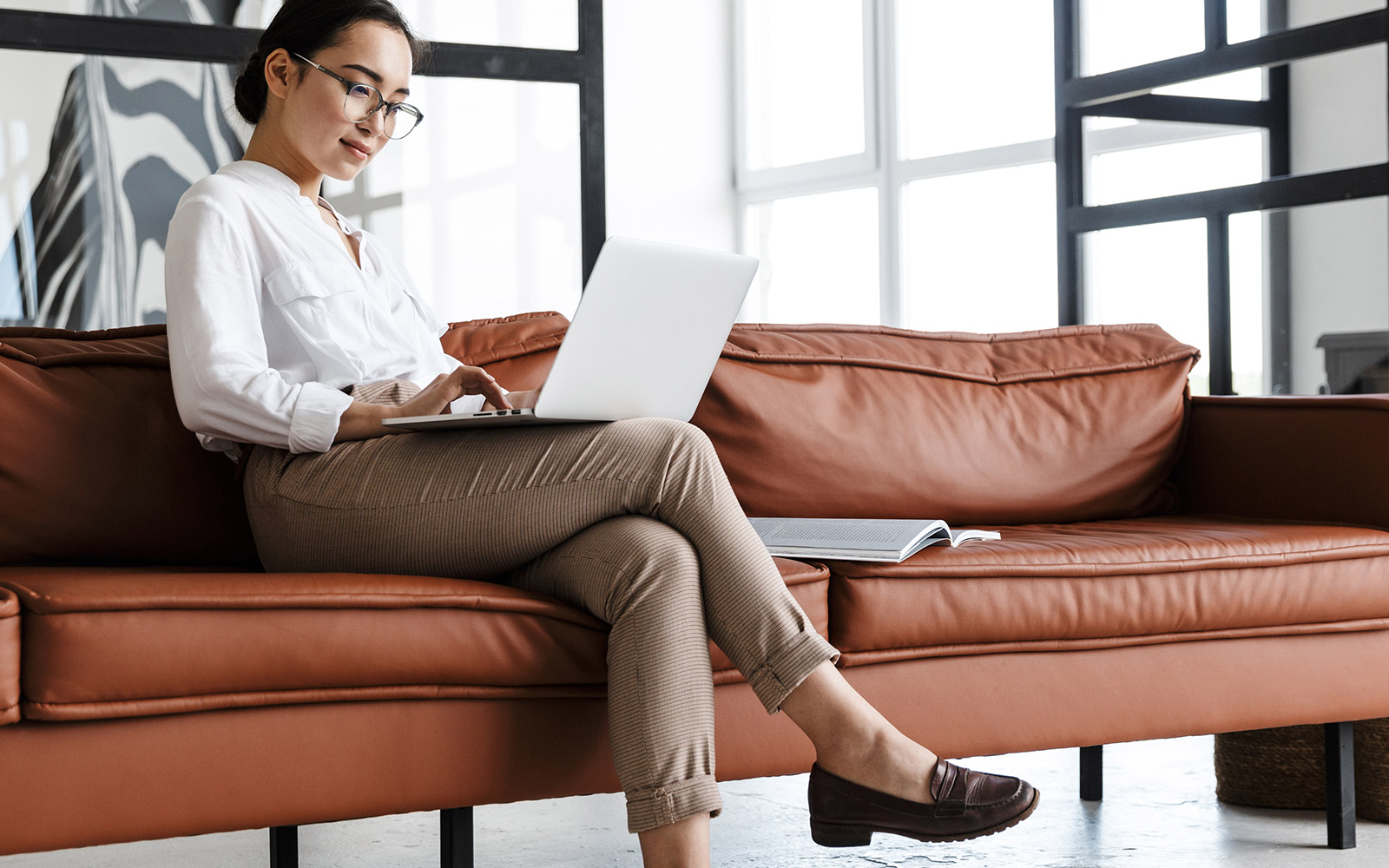 Woman sitting on a couch looking at her laptop