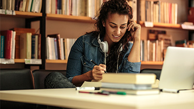 Woman studying in the library for her online college credit course
