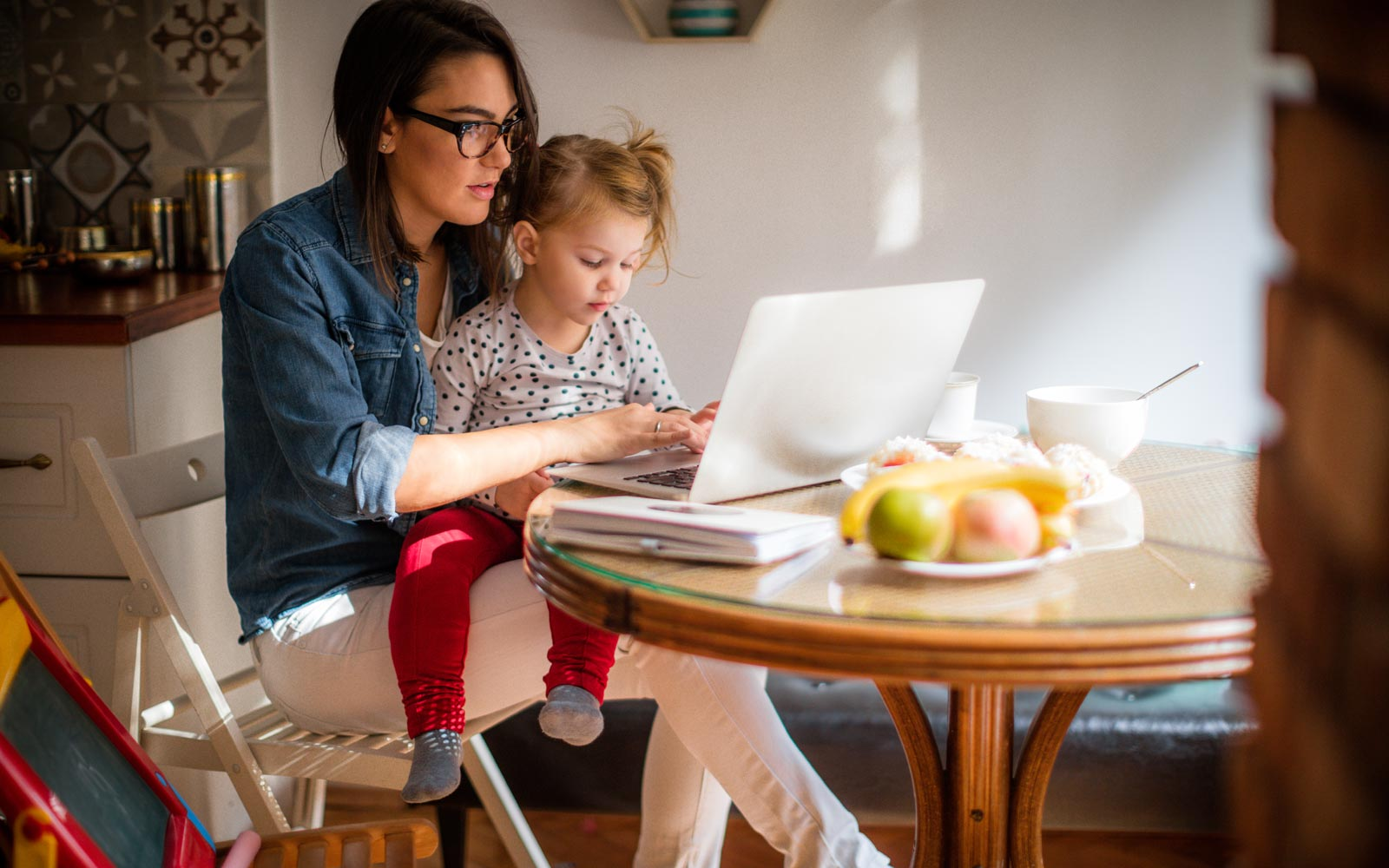 Young mother and child in kitchen studying online